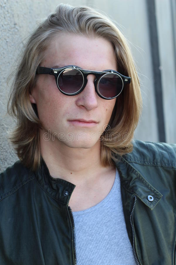 Homem novo considerável com cabelo louro e os óculos de sol longos isolados no fundo cinzento Tiro do estúdio da forma imagem de stock royalty free