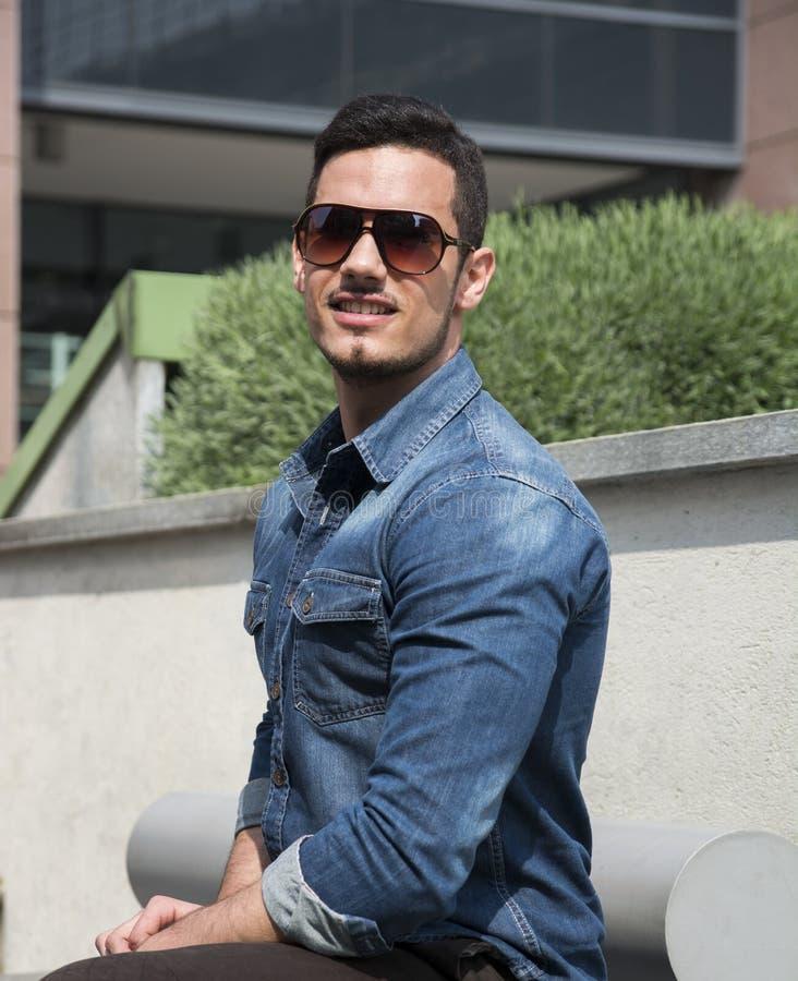 Homem novo considerável com camisa e óculos de sol da sarja de Nimes foto de stock