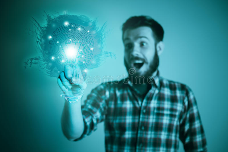 Homem novo considerável com o bulbo da ideia no azul imagens de stock