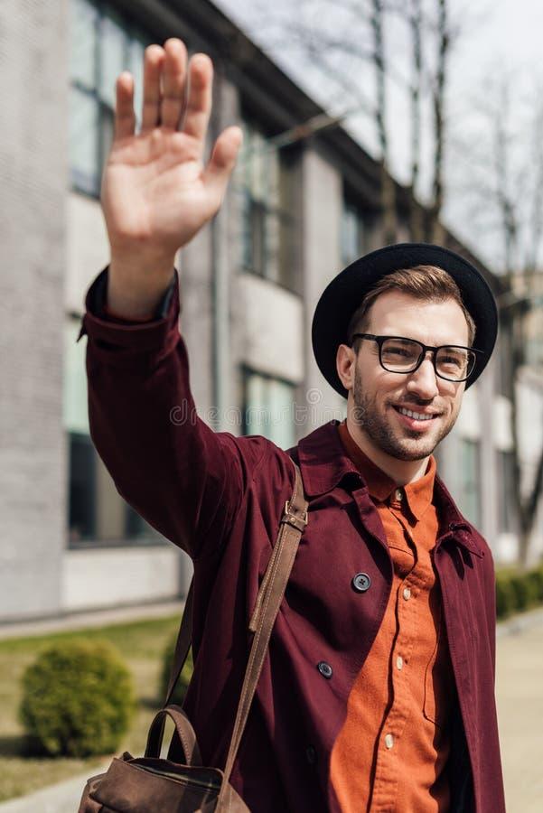 homem novo considerável com o saco que acena a ilustração royalty free