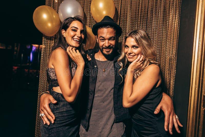 Homem novo considerável com os amigos fêmeas no clube noturno fotografia de stock royalty free