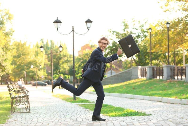 Homem novo considerável com a pasta que corre no parque fotografia de stock
