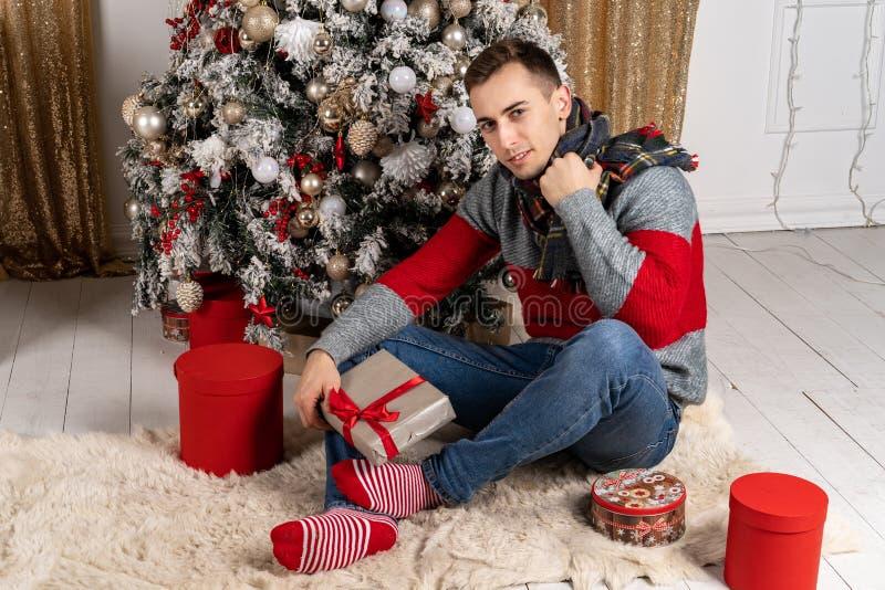 Homem novo considerável com um lenço que senta-se com os presentes na manta perto da árvore de Natal imagens de stock