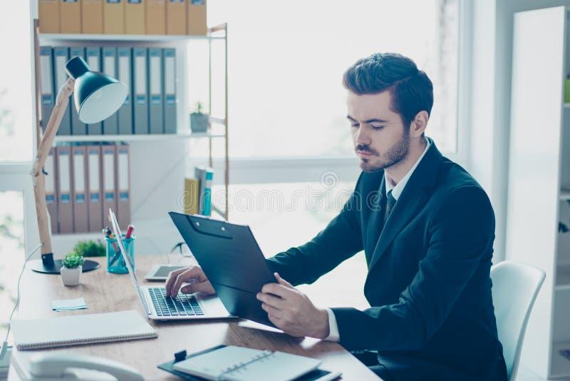Homem novo considerável concentrado no terno preto que senta-se na aba imagens de stock royalty free
