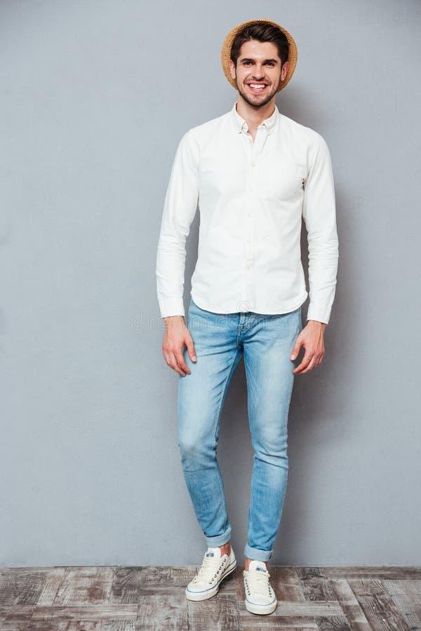 Homem novo considerável de sorriso na camisa, nas calças de brim e no chapéu brancos fotos de stock royalty free