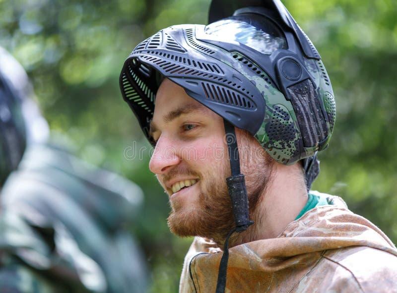 Homem novo considerável de sorriso na máscara aberta do paintball imagens de stock