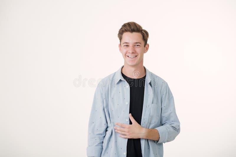 Homem novo considerável de vista amigável que veste a posição de sorriso da camisa azul sobre o fundo branco imagens de stock royalty free