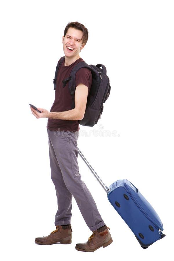 Homem novo considerável do comprimento completo com a mala de viagem e a trouxa que guardam o telefone foto de stock royalty free