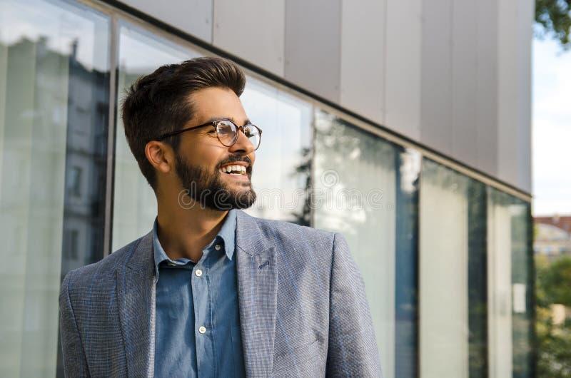 Homem novo considerável do retrato do close up na frente do sorriso moderno do escritório foto de stock royalty free