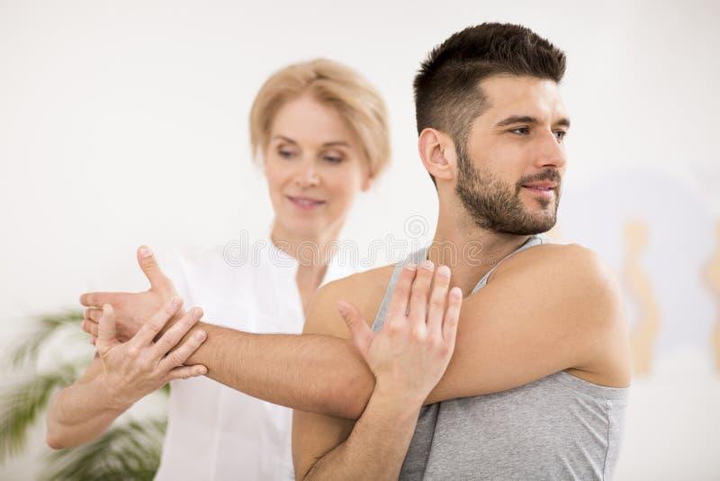 Homem novo consider?vel durante a sess?o da fisioterapia com doutor profissional fotos de stock
