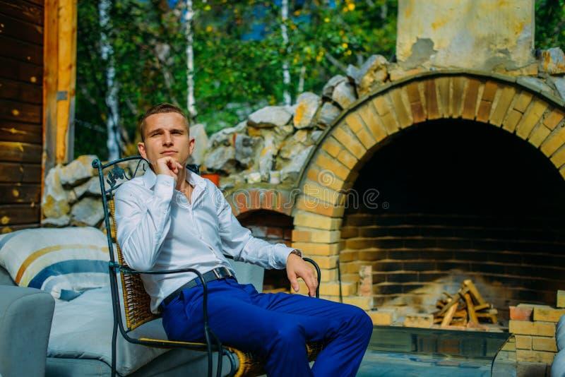 Homem novo considerável elegante que senta-se pela chaminé em uma varanda exterior do vintage fotos de stock