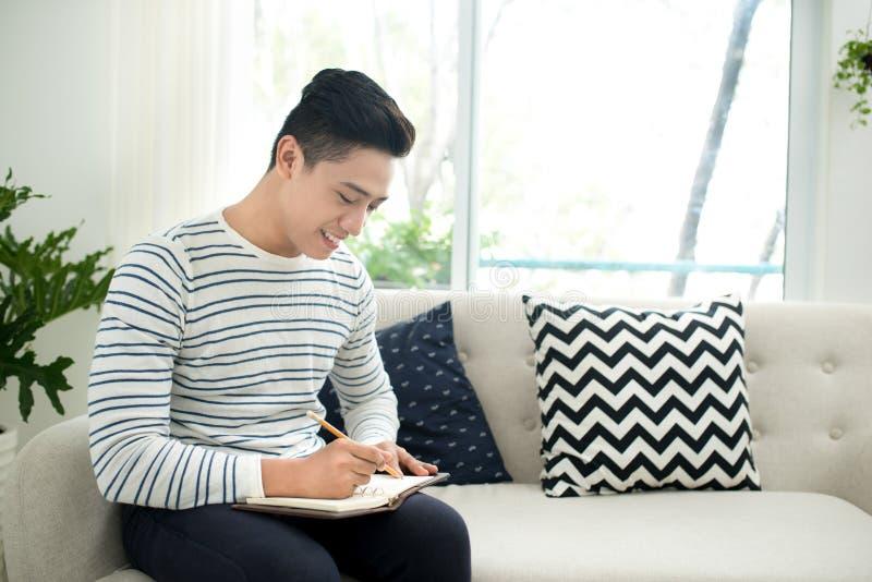 Homem novo considerável em casa que escreve escrevendo para baixo pensamentos no jou fotografia de stock