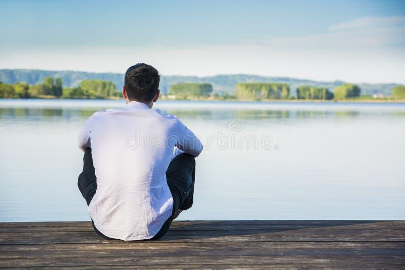 Homem novo considerável em um lago em um ensolarado, calmo foto de stock
