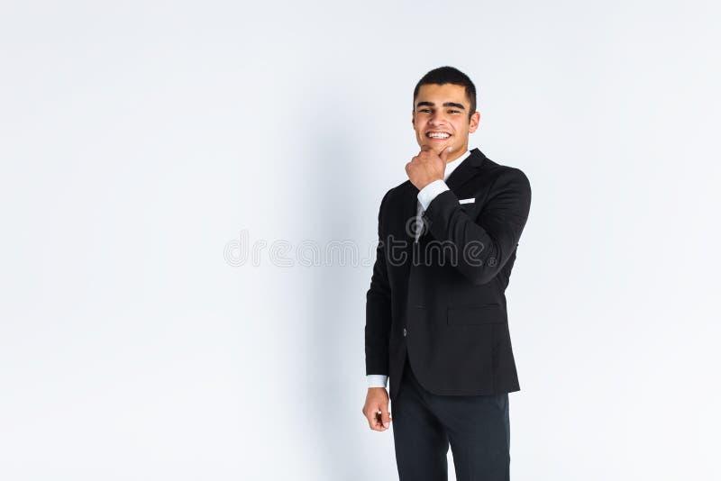 Homem novo considerável em um terno à moda, levantando em um fundo branco isolado fotos de stock