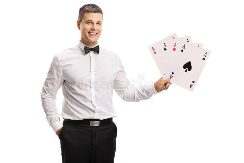 Homem novo considerável em um tux que guarda cartões de jogo imagens de stock royalty free