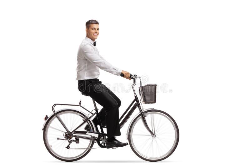 Homem novo considerável em um tux que monta uma bicicleta fotos de stock royalty free