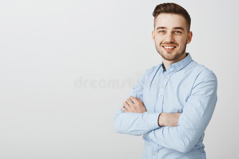 Homem novo considerável esperto e criativo ambicioso com cerda e penteado à moda na camisa do colarinho azul que guarda as mãos fotos de stock