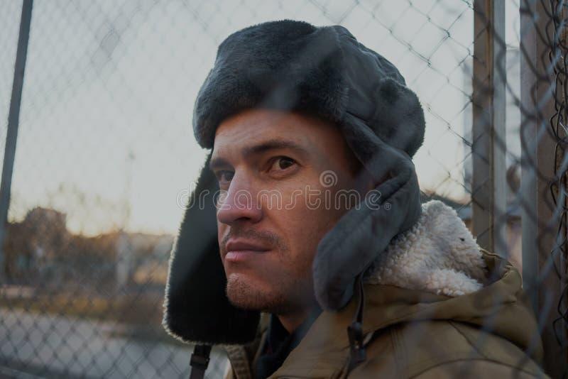 Homem novo considerável feliz no tampão com earflaps O homem novo no chapéu forrado a pele fotografia de stock