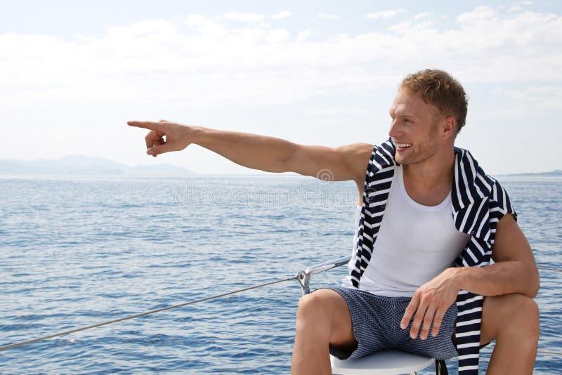 Homem novo considerável louro em um barco de navigação que aponta em algo fotos de stock royalty free