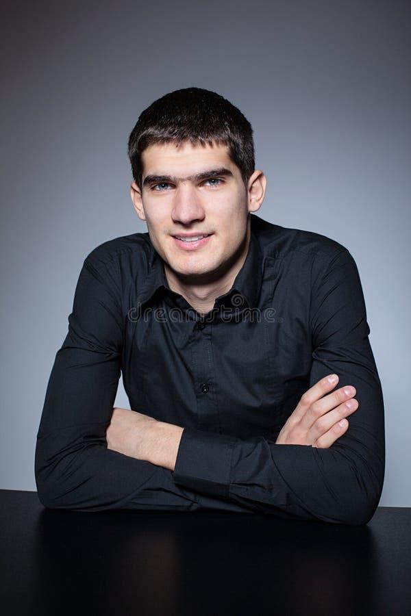 Homem novo considerável na camisa preta no fundo escuro fotos de stock royalty free