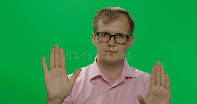 Homem novo considerável na camisa que diz não e que faz o gesto da parada com uma mão fotografia de stock royalty free