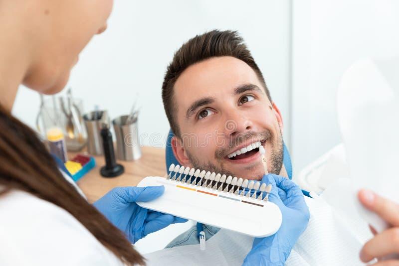 Homem novo considerável na clínica do stomatology foto de stock