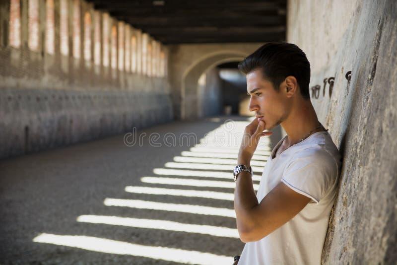 Homem novo considerável na construção velha contra a parede de tijolo fotografia de stock