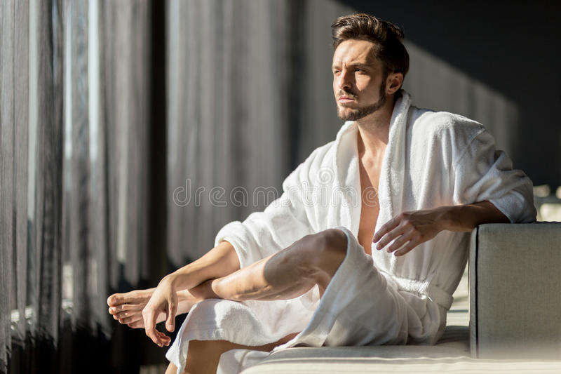 Homem novo, considerável na manhã que pensa ao sentar-se em um r fotografia de stock