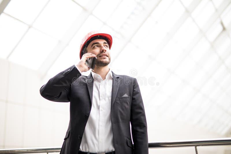 Homem novo considerável no capacete de segurança que guarda o modelo e que fala no telefone celular ao estar foto de stock