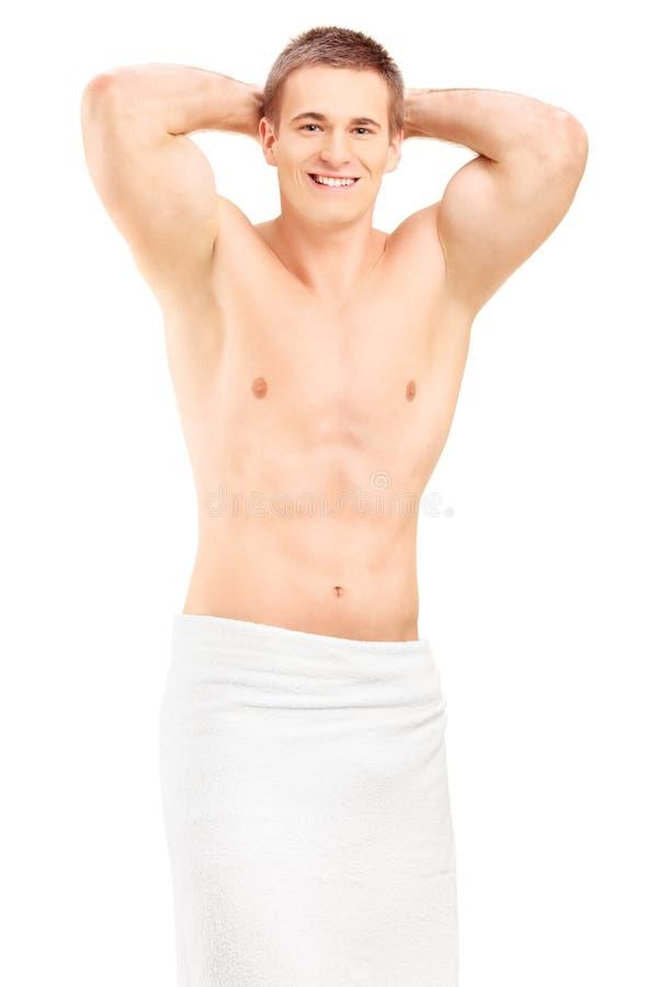 Homem novo considerável no levantamento de toalha foto de stock