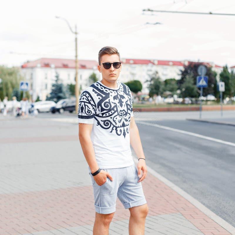Homem novo considerável no t-shirt e short que levanta no backgroun imagem de stock royalty free