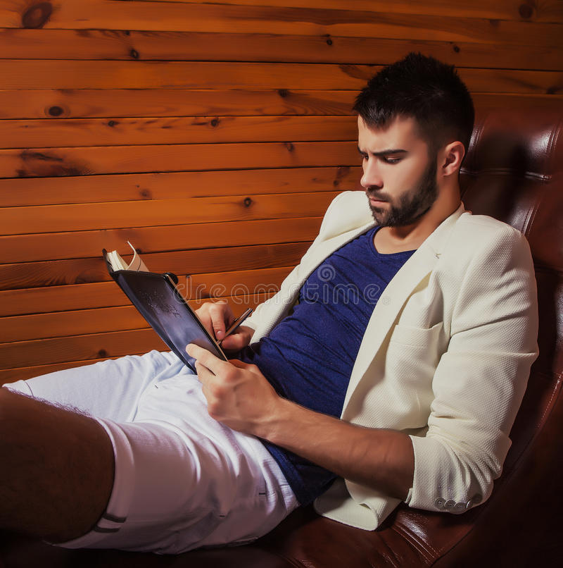 Homem novo considerável no terno branco que relaxa no sofá luxuoso com diário imagem de stock royalty free