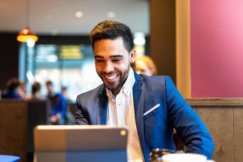 Homem novo considerável no terno usando o portátil fotos de stock