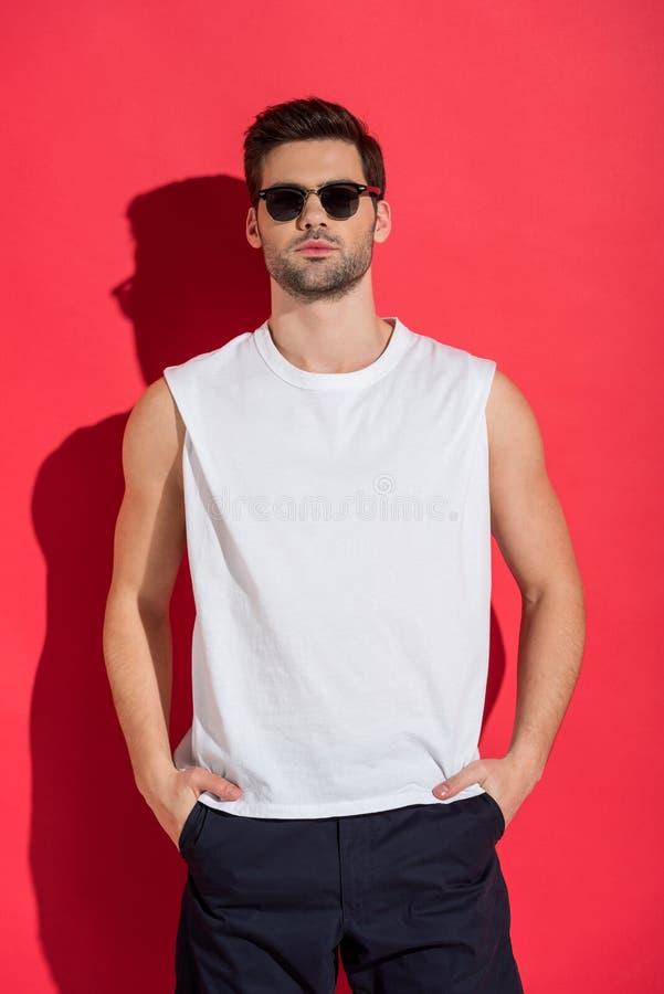 homem novo considerável nos óculos de sol que estão com mãos em uns bolsos e que olham a câmera foto de stock royalty free