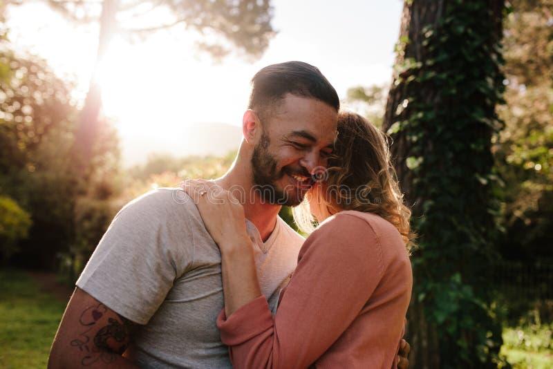 Homem novo considerável que abraça sua amiga em um parque fotos de stock