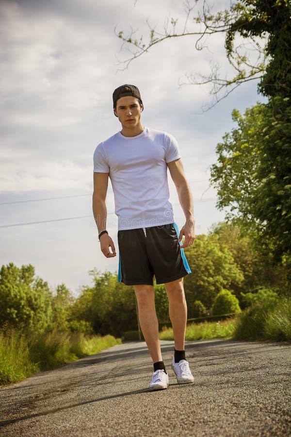Homem novo considerável que anda e que trekking na estrada imagem de stock