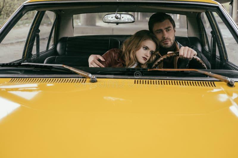 homem novo considerável que conduz o carro e que abraça a amiga pensativa bonita fotos de stock royalty free