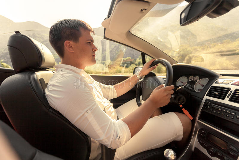 Homem novo considerável que conduz o convertible no dia ensolarado imagens de stock