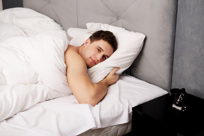 Homem novo considerável que encontra-se na cama imagens de stock royalty free