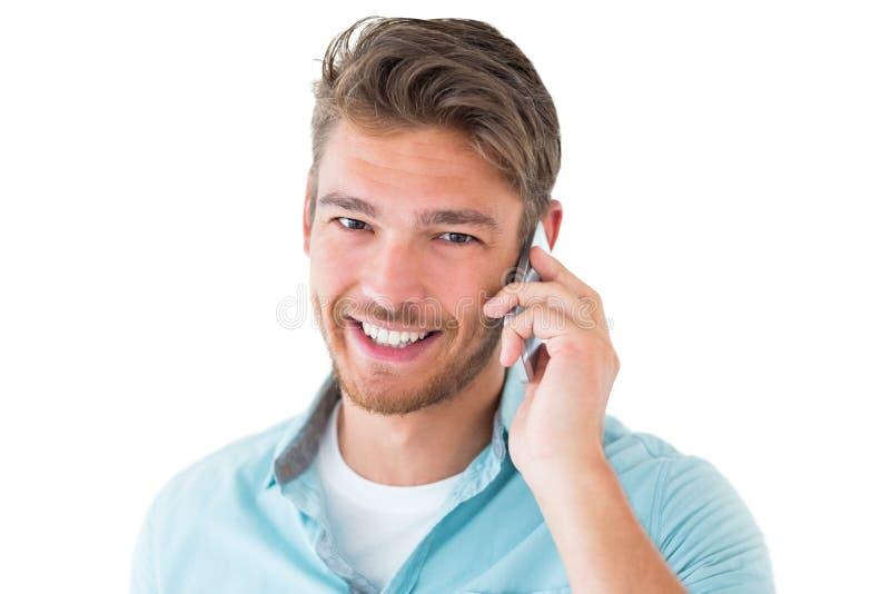Homem novo considerável que fala em seu smartphone foto de stock