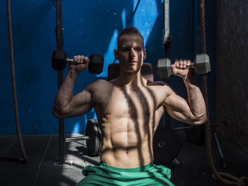 Homem novo considerável que faz exercícios do Abs no banco do gym foto de stock