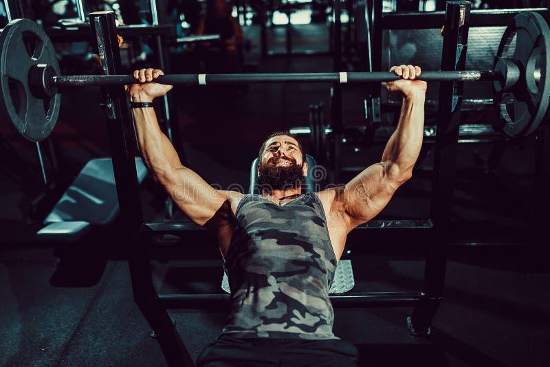 Homem novo considerável que faz o exercício da imprensa de banco no gym imagens de stock royalty free