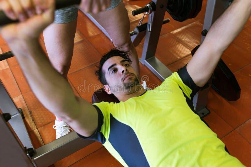 Homem novo considerável que faz o exercício muscular no gym foto de stock royalty free