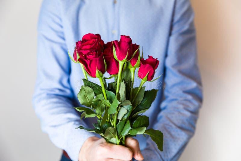 Homem novo considerável que guarda o ramalhete cor-de-rosa vermelho, surpresa romântica do dia de Valentim, amor, flores imagem de stock