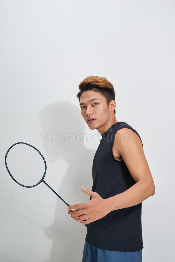 Homem novo considerável que guarda a raquete e a peteca de badminton em g imagem de stock