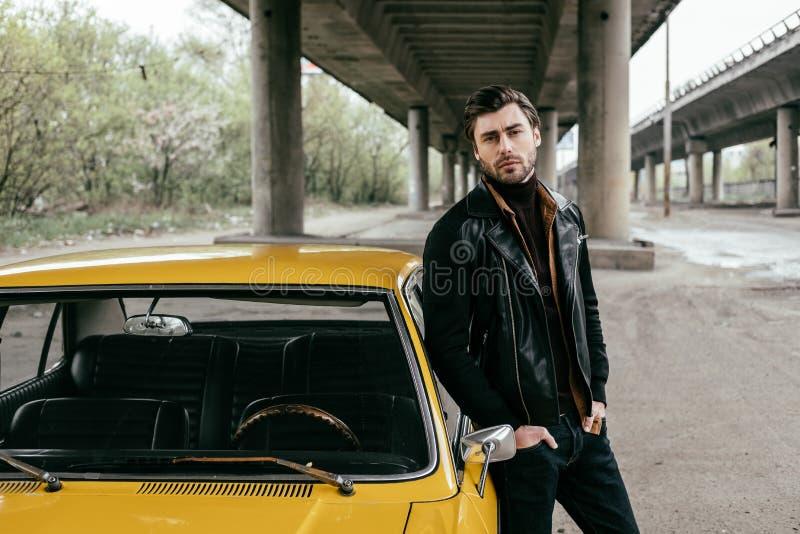 homem novo considerável que inclina-se no automóvel antiquado e na vista fotografia de stock