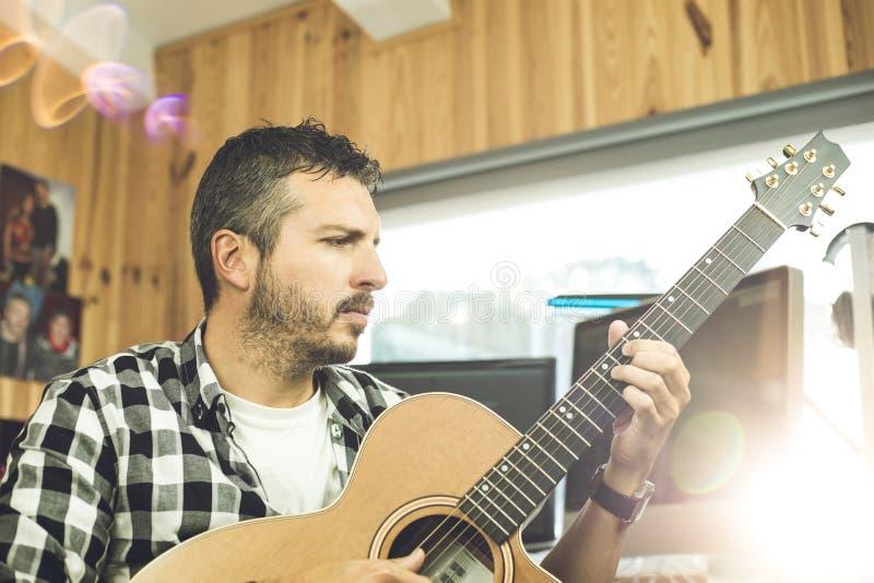 Homem novo considerável que joga a guitarra Músico que joga a guitarra espanhola imagens de stock