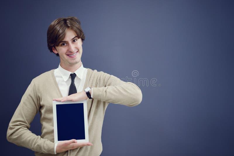 Homem novo considerável que mostra algo em uma tabuleta, isolada sobre o fundo cinzento fotos de stock