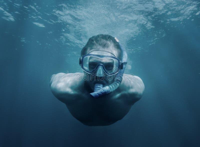 Homem novo considerável que nada debaixo d'água fotos de stock