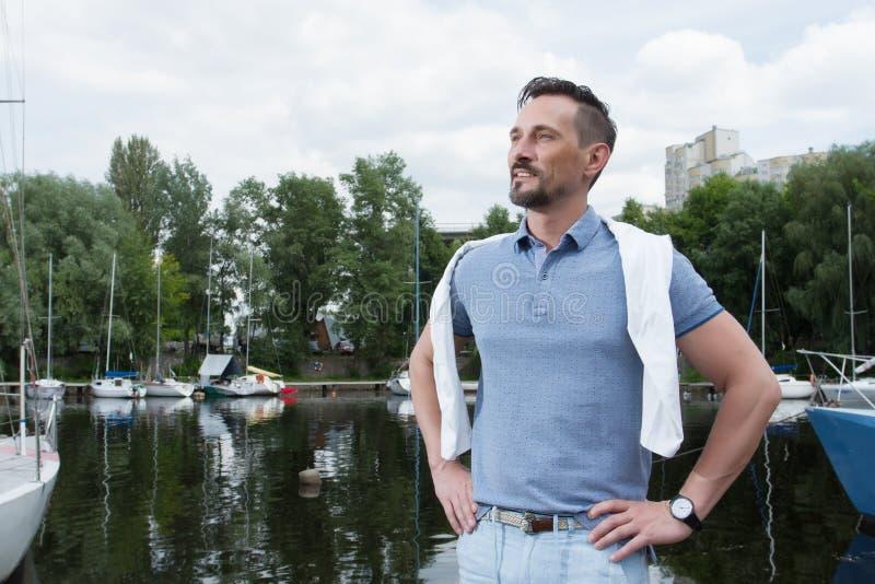 Homem novo considerável que olha distante com fundo e os barcos verdes da floresta Homem do estilo do esporte de água fotografia de stock